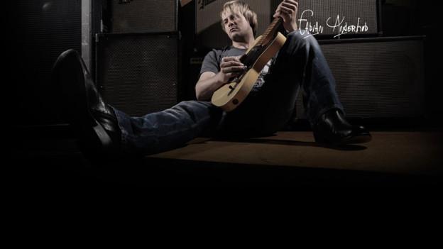 Stefan Anderhub mit Gitarre am Boden liegend.