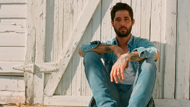 Ryan Bingham sitzt auf einer Türschwelle. Seine Arme sind tätowiert.