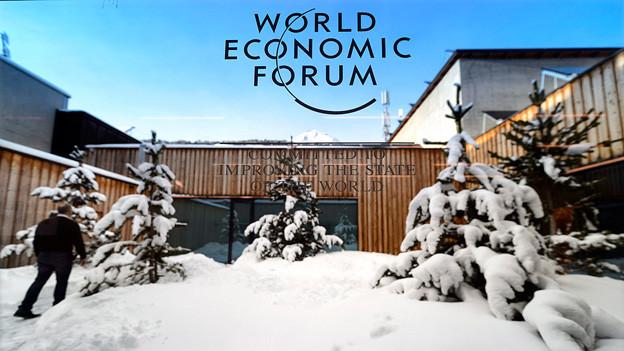 Aufschrift «World Economic Forum» auf einer Glasscheibe, dahinter Blick auf die Winterlandschaft.