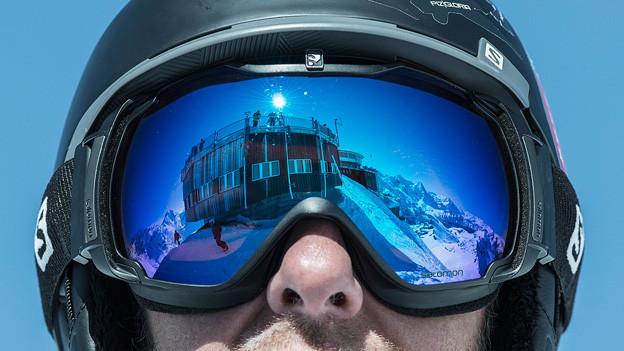 Mann trägt eine spiegelnde Skibrille.