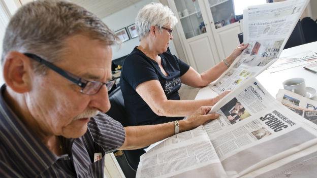 Älterer Mann und ältere Frau lesen Zeitung.