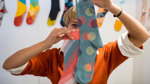 Frau hält Socken hoch