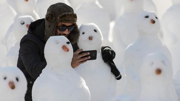 Mann macht Selfie mit Schneemann.