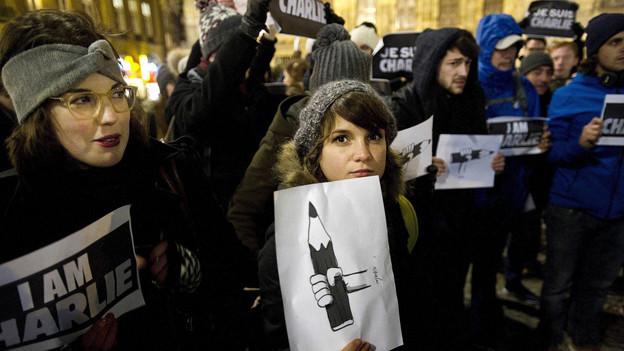 Menschen demonstrieren für Meinungsfreiheit.