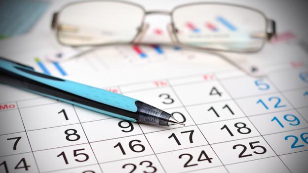 Kalender mit Beistift und Brille.