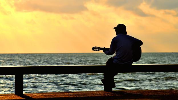 Mann mit Gitarre am Meer.