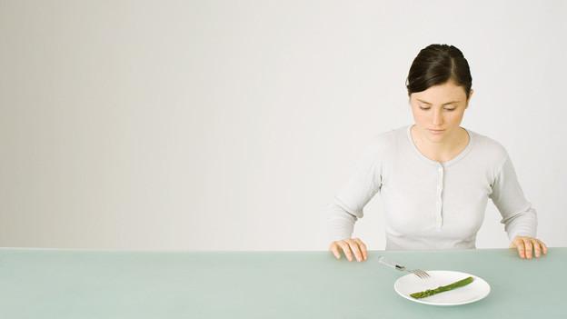 Eine junge Frau sitzt von einem Teller mit einer Spargel darauf.
