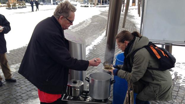 Mann schenkt Frau auf der Gasse Suppe in ein Geschirr.