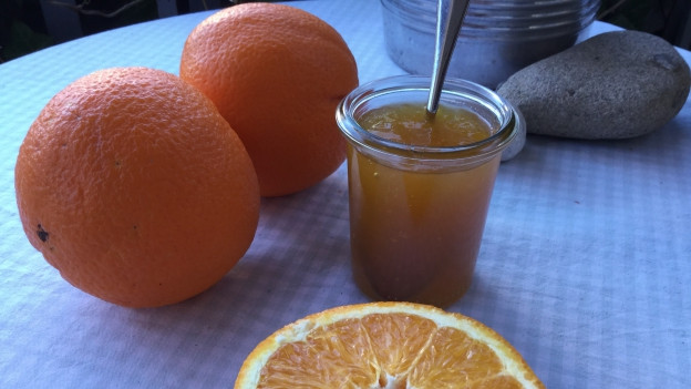 Orangen und ein Glas Konfiture auf dem Tisch.