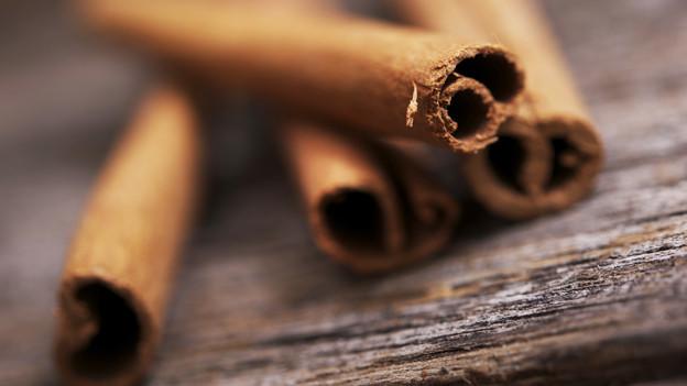 Nahaufnahme von Zimtstengel auf einem Holztisch.
