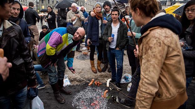 Menschen grillieren Würste am Zürcher Sechseläuten.