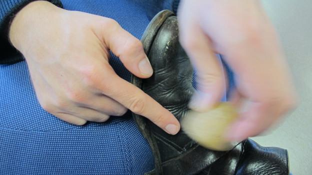 Jemand reibt einen Schuh mit einer Kartoffel ein.