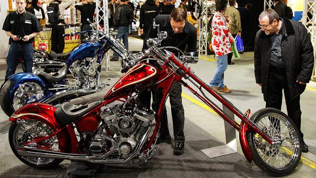 Zwei Männer betrachten ein ausgestelltes Motorrad.