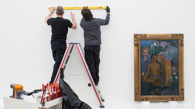 Zwei Männer hantieren im Museum mit einer Wasserwaage an der Wand.