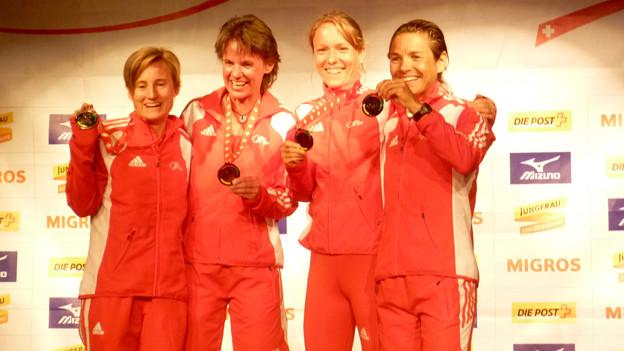 Frauen mit Medaillen.