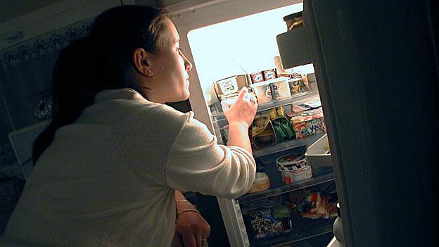 Frau nimmt nachts etwas aus dem Kühlschrank.