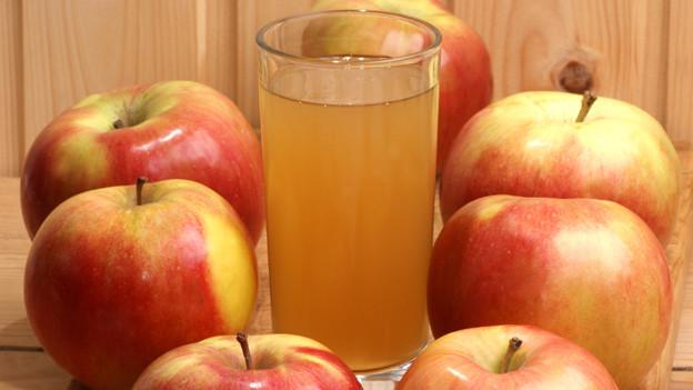 Ein Glas Most in Mitten von Äpfeln.
