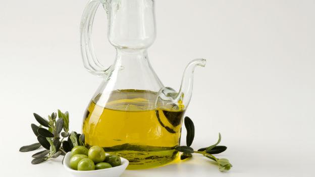 Eine Flasche Olivenöl mit Oliven