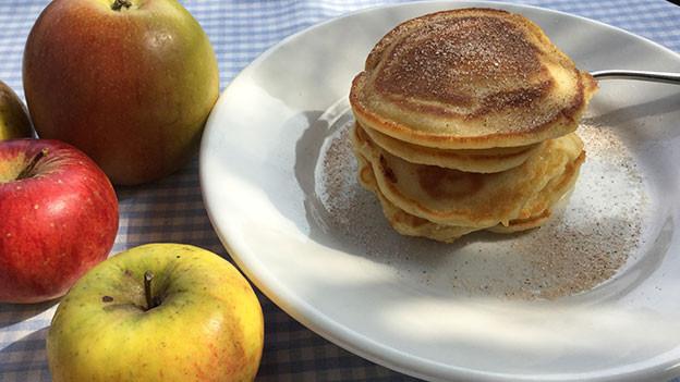 Pancakes aus Buttermilch sind auf einem Teller angerichtet. Der Tisch ist mit Äpfeln dekoriert.