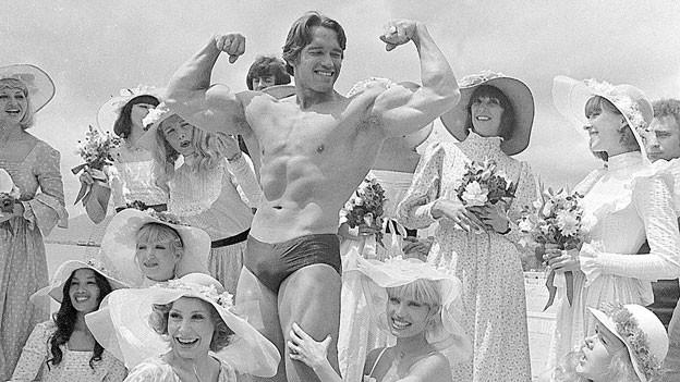 Muskelprotz Arnold Schwarzenegger umringt von Frauen am Strand.
