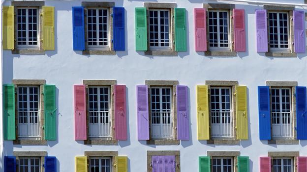 Hausfassaede mit unterschiedlich farbigen Fensterläden.