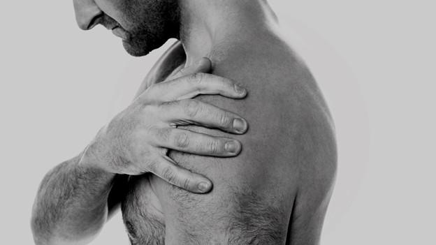 Mann fasst sich an die Schulter.
