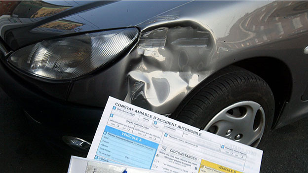 Blechschaden an einem Auto. Davor steht ein Mann mit einem Schadenformular.