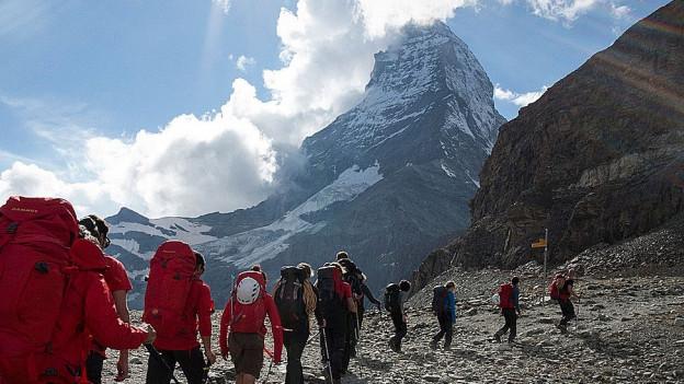 Wanderer auf dem Weg Richtung Matterhorn, der Gipfel im Hintergrund.