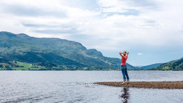 Frau steht an einem See und streckt sich dem Himmel entgegen.