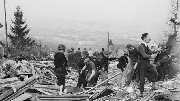 Menschen räumen das Trümmerfeld auf.