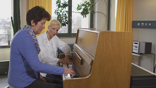 Frau sitzt mit einer anderen Frau am Klavier.