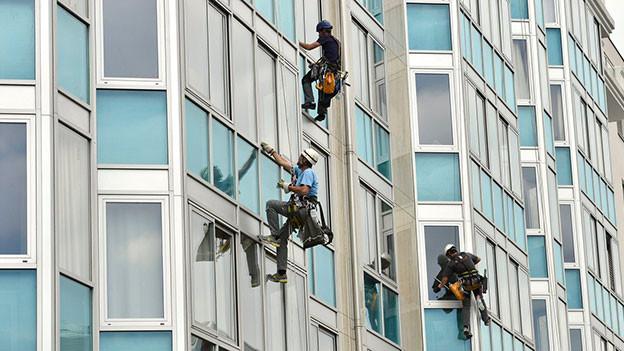 Alpinisten seilen sich an einer Glasfassade ab, um die Fenster zu putzen.