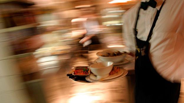 Kellner rennt mit einer Bestellung durch ein Restaurant.