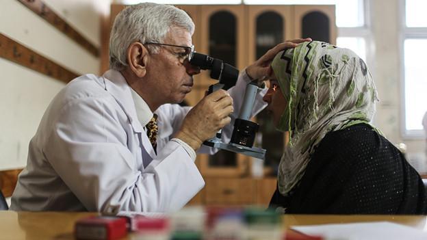 Arzt schaut mit einem Gerät einer Frau in die Augen.