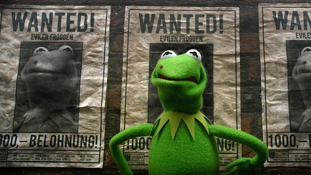 Froschpuppe vor Plakaten mit der Aufschrift «Wanted».