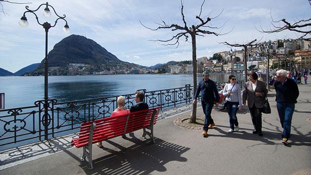 Menschen flanieren in Lugano am See.