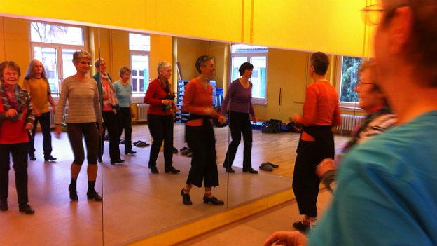Stepptanzgruppe tanzt vor Spiegel.