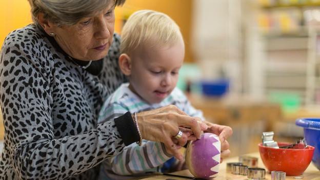 Eine Frau schnitzt mit ihrem Enkel eine Rübe.