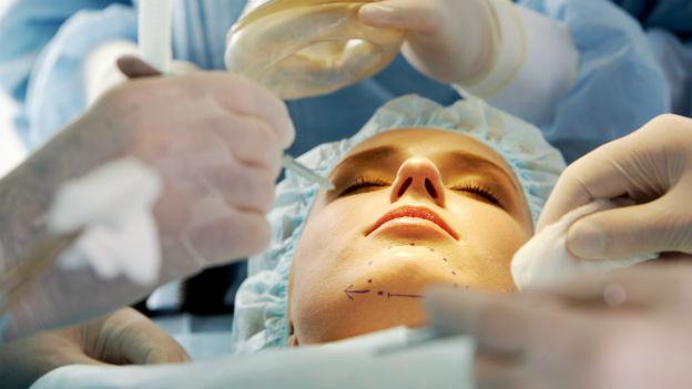 Frau wird im Gesicht operiert.