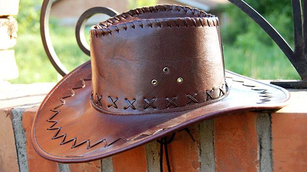 Cowboyhut liegt auf Mauer.
