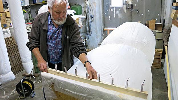 In seiner Werkstatt in Stäfa montiert Heinz Wahrenberger seinem letzten Böögg ein paar Böller an die Füsse.