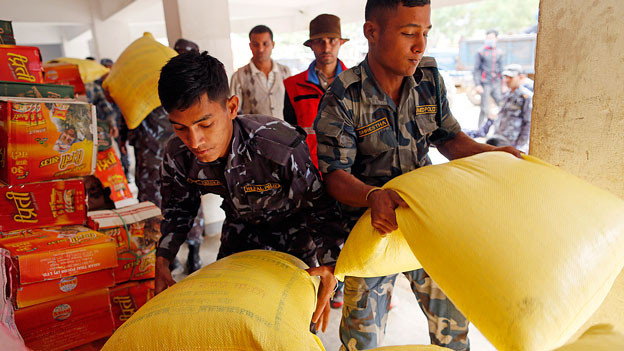 Nepalesische Soldaten stapeln Lebensmittelsäcke.