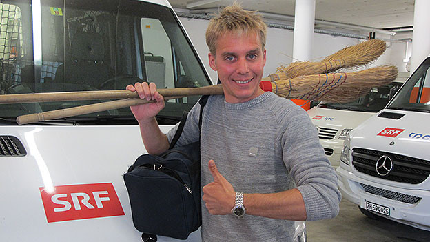 Reto Scherrer mit Tasche und Besen vor dem Reporterwagen.