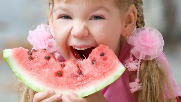 Mädchen beisst in eine Wassermelone.