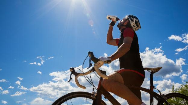 Fahrradfahrer trinkt aus einer Flasche.
