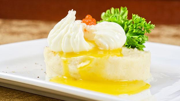 Pochiertes Ei auf Kartoffelpüree mit orangem Kaviar.