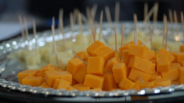 Cheddar Käsestückchen auf einer Platte angerichtet.