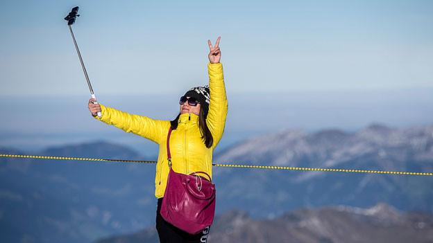 Eine chinesische Touristin macht auf dem Berggipfel ein Selfie.