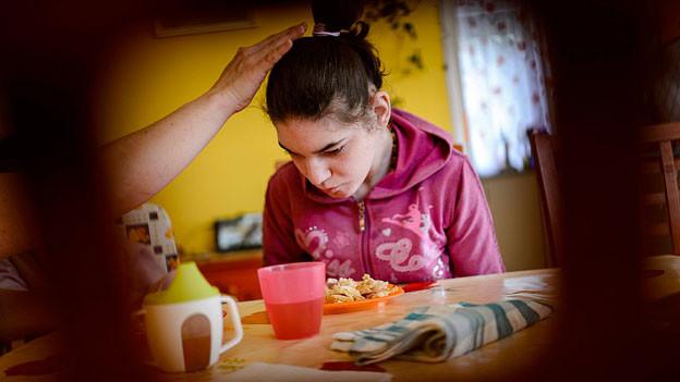 Ein Mädchen sitzt am Tisch, eine Hand berührt behutsam ihr Haar.