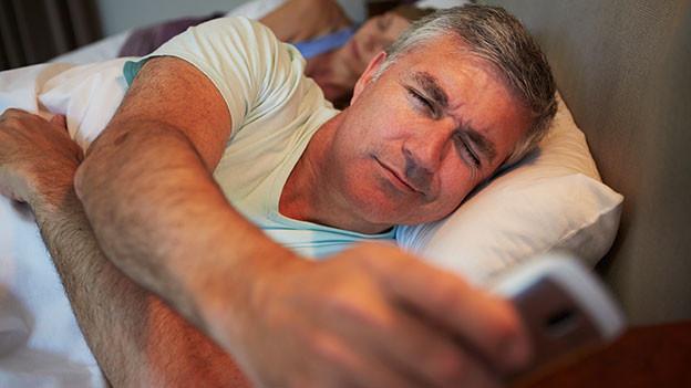Ehepaar im Bett. Die Frau schläft, der Mann greift zum Handy.